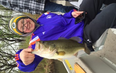 NICE CATCH: Freshman Alex Pillath holds up a fish he caught at practice on Busse Lake on May 1 preparing for sectionals. The team has the home advantage at sectionals which take place today in Busse Woods. State will take place at Carlyle Lake in Carlyle May 20-21.